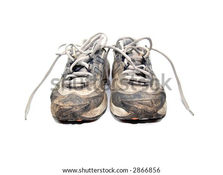 worn our jogging shoes with mud, isolated on white background