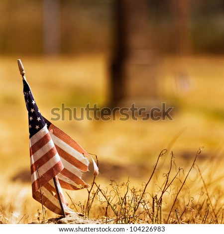 Worn out american flag against a dried out field background.
