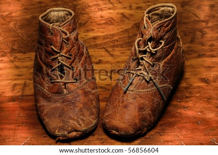 Worn out antique leather baby shoes on wooden floor