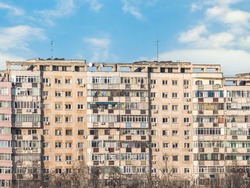 Worn out apartment building from the communist era against blue sky in Bucharest Romania. Ugly traditional communist housing ensemble