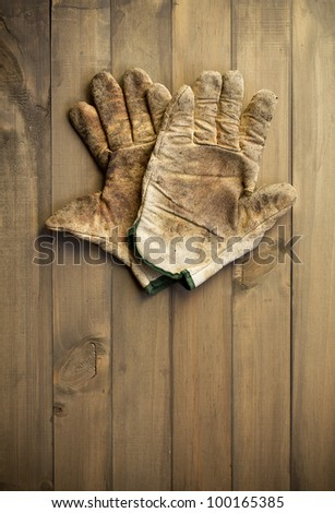 worn out working gloves against wooden surface. add your text