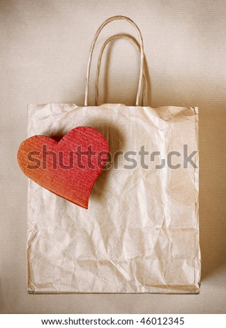 Worn paper bag with red cardboard heart over wrapping paper