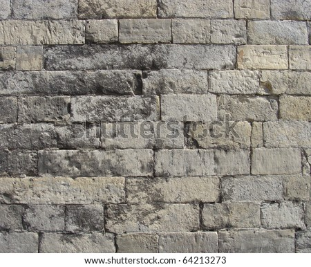 worn very old large stone wall in gray and beige