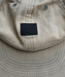 Worn vintage hat cap top view with empty logo label, creative street appeal flyer background texture concept