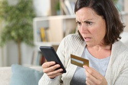 Worried adult woman paying online on smart phone with credit card sitting on the sofa at home