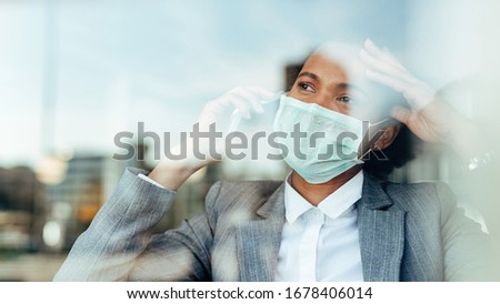Worried African American businesswoman wearing protective mask and talking on mobile phone while looking through the window. The view is through the glass.