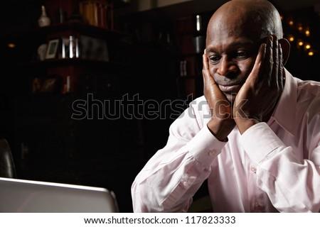 Worried african guy in pink shirt sitting at laptop