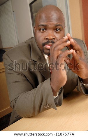 Worried and anxious businessman sitting at a desk and tapping his fingers