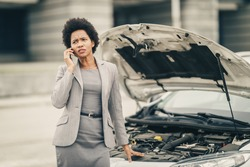 Worried black business woman calling for help after her car breakdown on the street.