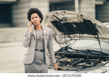 Worried black business woman calling for help after her car breakdown on the street. Stock photo ©