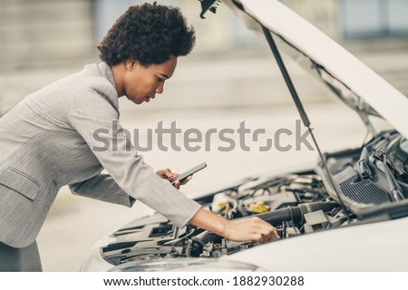 Worried black woman using smartphone and looking under the hood of her car while calling for help after vehicle breakdown on a roadtrip. Stock photo ©