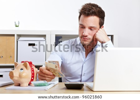 Worried business man with money and piggy bank in office