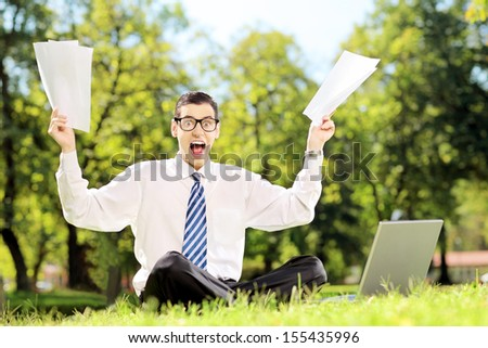 Worried businessman holding documents and shouting seated on a green grass in a park