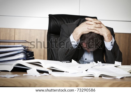 Worried businessman in dark suit sitting at office desk full with books and papers being overloaded with work.