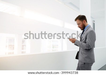 Worried businessman is reading e-mail on mobile phone from investor about suppression of the financing of his project, while is standing in office interior near copy space for your advertising content