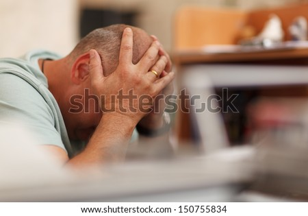 Worried businessman sitting in front of his computer with his head in his hands