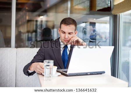 worried businessman sitting in front of laptop in cafe