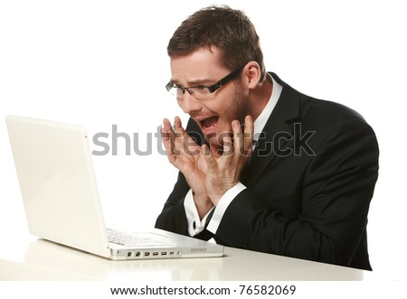 Worried businessman wearing glasses, working on laptop, isolated on white