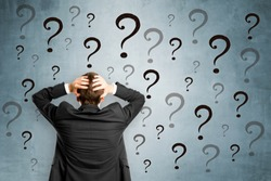 Worried businessman with question marks. Confusion and enquiry concept
