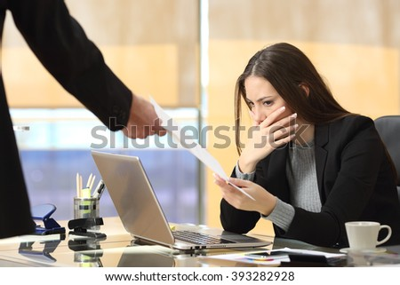 Worried businesswoman receiving a notification from a colleague in her workplace at office