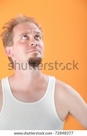 Worried Caucasian man on orange background looks up
