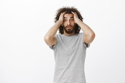 Worried desperate aduly male freelancer with afro haircut in trendy striped t-shirt, holding hands on head and lifting eyebrown, feeling nervous and shocked, seeing work not finished in time