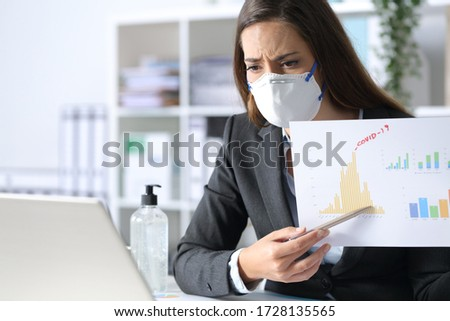 Worried executive woman wearing protective mask shows bad results report on videocall on laptop after covid-19 at the office