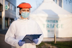 Worried exhausted and stressed frontline UK doctor,wearing PPE and face shield,out of hospital patient triage tent quarantine,special US COVID-19 intensive care unit facility for close contact cases