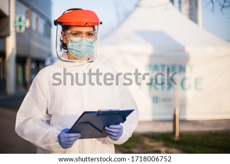 Worried exhausted and stressed frontline UK NHS doctor,wearing PPE & face shield,out of hospital patient triage tent quarantine,special US COVID-19 intensive care unit facility for close contact cases