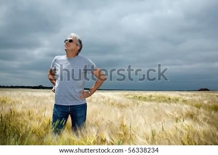 Worried farmer  scrutinizing a threatening cloudy sky.