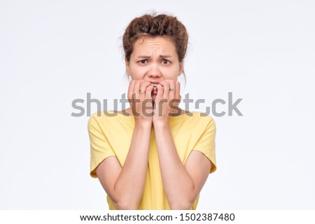 Worried female looks nervously, bites finger nails. Nervous excited asian woman worries wants to show her best #1502387480