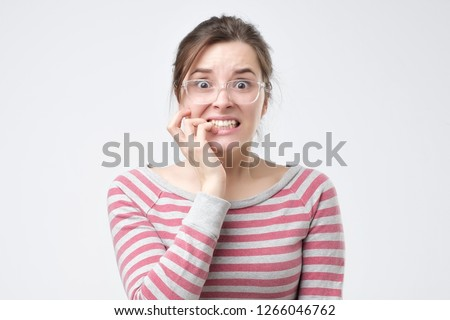 Worried female looks nervously, bites finger nails, watches moving horror film. Nervous excited young woman worries before job interview