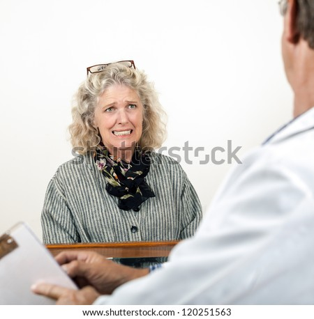 Worried frightened mature woman consults with doctor in his office. Focus is on the woman.