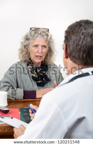 Worried frightened mature woman consults with doctor in his office. Focus on the woman.