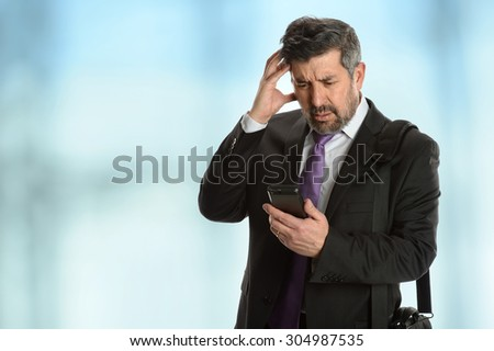Worried Hispanic businessman looking at cellphone