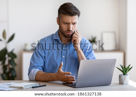 Worried Male Entrepreneur Having Problems With Laptop Computer At Work, Talking With Customer Support On Cellphone, Concerned Man Suffering Bad Internet Connection At Workplace In Office, Free Space Photo stock ©