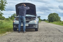 Worried man holding his head by hands standing near his old broken car with raised hood on the road