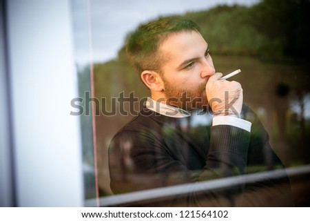 Worried man smoking a cigarette close to the window,Italy