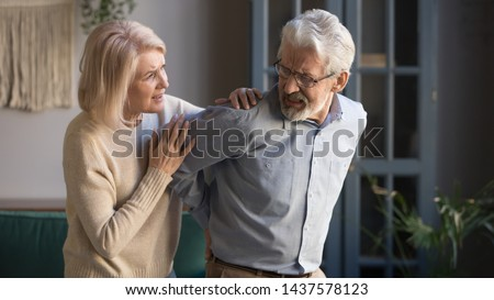 Worried mature wife supporting senior husband feel sudden back pain muscles tension injury at home, upset grandfather touching back having lower lumbago backache, old couple osteoarthritis concept