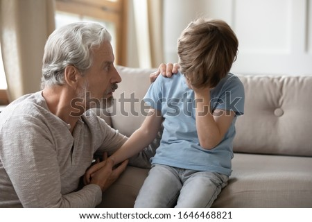 Worried middle aged hoary man supporting little offended grandchild suffering from bullying. Unhappy mature older grandfather asking forgiveness to stressed small kid boy feeling depressed at home. Stock photo ©