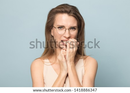 Worried millennial woman in eyeglasses folded hands together near mouth, gnawing nails, feels uncertain, stressed, confused female with frighten or panic gesture, isolated on blue studio background.