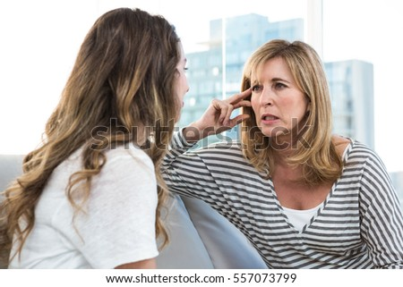 Worried mother talking to daughter on sofa