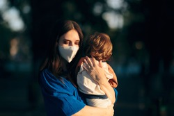 Worried Mother Wearing Face Mask Holding her Child. Mom feeling anxious for the future during pandemic health crisis