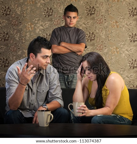 Worried Native American couple with upset son indoors