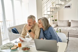 Worried old senior couple checking bank documents at home. Serious mature retired family reading paper bills, calculating taxes, planning retirement finances, household expenses, having money problems