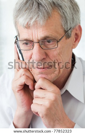 Worried older man talking on phone