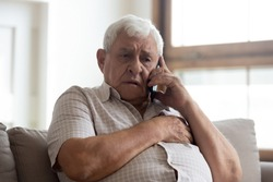 Worried older unhealthy man sitting on couch, making emergency 911 call, having painful feelings in chest, heart attack disease symptoms. Unhappy frustrated elderly grandfather listening to bad news.