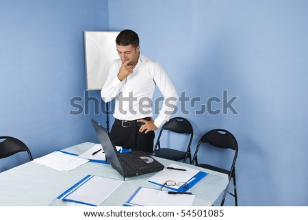 Worried or pensive  business man waiting in a meeting room for his colleagues and  holding his hand to face