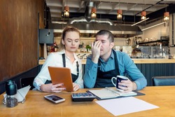 Worried owners in empty restaurant calculating finances - Coronavirus pandemic crisis - Bankrupt concept of Small entrepreneurs SME - Overwhelmed young woman and man with headache