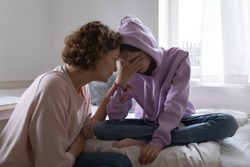 Worried parent young mom comforting depressed crying teen daughter bonding at home. Loving understanding mother apologizing or supporting sad teenage girl having psychological puberty problem concept.